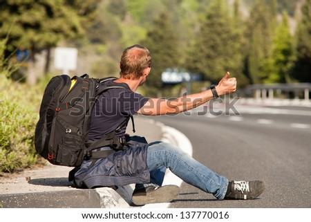 Hitchhiker traveler sitting on the roadside of the mountain highway - stock photo