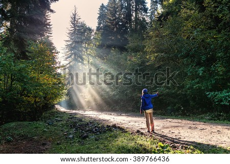 Hitchhiker young woman on the road in forest with fog.  Vintage style photo from a young woman is hitch-hikaing - stock photo
