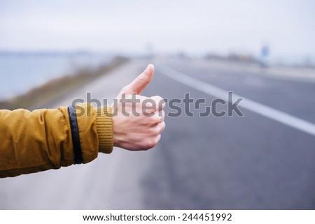 Hitchhikers sign thumb up at road - stock photo