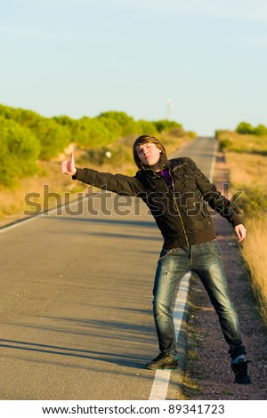 Hitchhiking youngster quite desperate to get a lift - stock photo