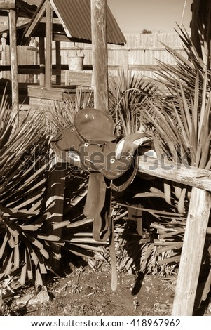 hitching post and saddle, parking from a bygone era - stock photo