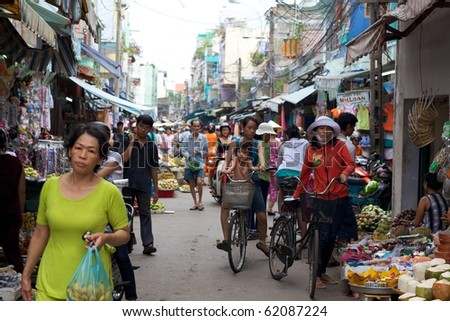 HO CHI MINH CITY- CIRCA JUNE 2010: Crowded marketplace with street vendor in Ho Chi Minh City, Vietnam selling produce and wares on the sidewalk (Ho Chi Minh City, Vietnam - CIRCA June, 2010) - stock photo