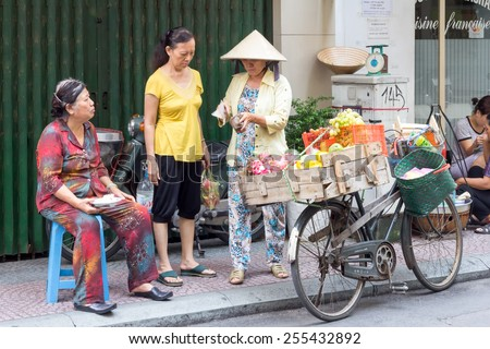 Ho Chi Minh City-Oct 31st2013: Vendor on bicycle selling to customers. Street vendors can be found all over the city. - stock photo