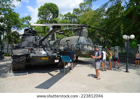 HO CHI MINH CITY (SAIGON) - MARCH 16, 2014: Tourist visitors looking at a U.S. Army tank and helicopter, at the War Remnants Museum, in Ho Chi Minh City (Saigon), Vietnam.
