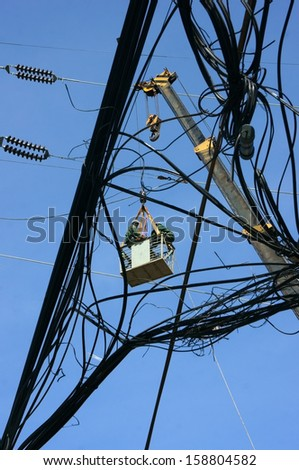 HO CHI MINH CITY, VIET NAM- APRIL 29: Electrician working among electric wire network, worker climd high and working to repair cable as spider under blue sky, Sai Gon, Vietnam, April 29, 2013    - stock photo