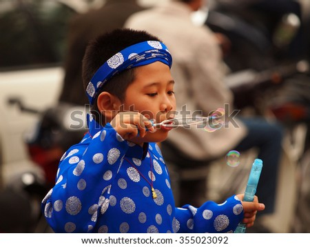 HO CHI MINH CITY, VIET NAM- FEB16:,Portrait of a  Asian  boy on traditional festival costume. Cute little Vietnamese boy  in ao dai dress smiling. Tet holiday. Lunar New Year Vietnam, Feb 16, 2015 - stock photo