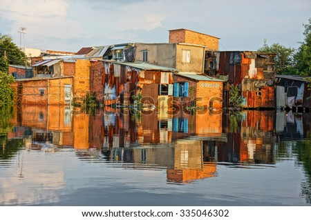 HO CHI MINH CITY, VIET NAM- OCT 10: Group of riverside downgrade house with red brick wall, poor residence near canal, danger and  unsafe life in climate change situation, Vietnam, Oct 10, 2014 - stock photo