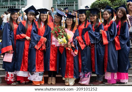 HO CHI MINH CITY, VIETNAM- AUG 8 : Group of women student in gown uniform standing, hold hand with smile on graduate ceremony at university, young girl happy with bright future, Viet Nam,  Aug 5, 2014 - stock photo