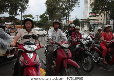 HO CHI MINH CITY VIETNAM - AUGUST 19: unidentified men and women rides motorbikes, on August 19, 2011, in Ho Chi Minh City, Vietnam. Ho Chi Minh City, also named Saigon, is the largest city in Vietnam