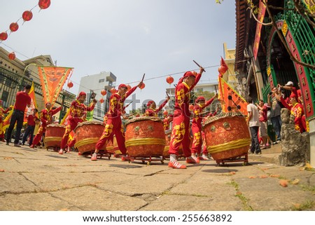 HO CHI MINH CITY, VIETNAM - FEBRUARY 18, 2015 : A group of boys beating their drums and dancing in the show of lion dance during the Tet Lunar New Year celebrations at Cho Lon, Saigon. - stock photo