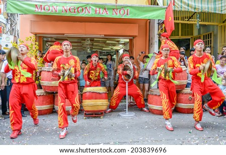 HO CHI MINH CITY, VIETNAM - FEBRUARY 1: A group of unidentified local boys beating their drums and dancing during the Tet Lunar New Year celebrations on February 1, 2014 in Ho Chi Minh City, Vietnam. - stock photo