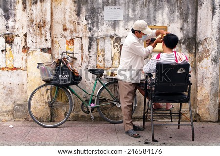 HO CHI MINH CITY, VIETNAM - JAN 20: An unknown man is having hair cut on January 20, 2013 in Ho Chi Minh City, Vietnam. This mobile or street barber shop is very convenient and suitable for the poor.
