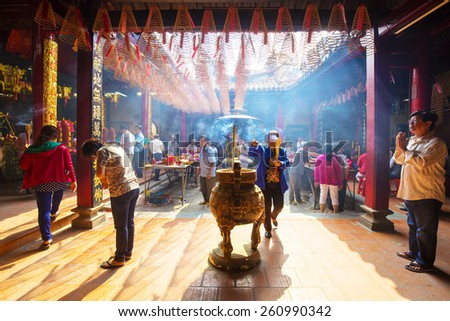HO CHI MINH CITY, VIETNAM - 05 MAR, 2014: people praying and burning incense on Chinese temple during Lunar new year festival in Hochiminh city - stock photo