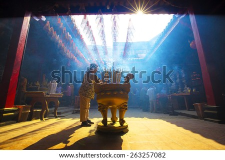 HO CHI MINH CITY, VIETNAM - 04 MAR, 2014: people praying and burning incense on Chinese temple during Lunar new year festival in Hochiminh city - stock photo