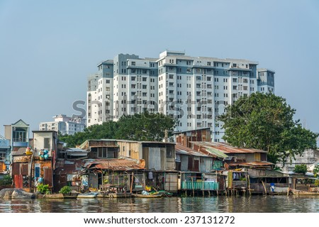 HO CHI MINH CITY, VIETNAM - OCTOBER 11:People live in slums which was built above canals in Ho Chi Minh city, the building in the background will be their new home soon. - stock photo