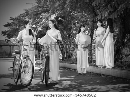 Ho Chi Minh City, Vietnam - September 13rd, 2015: Group student girls are chatting academic exchange with long dress and hat beautiful leaf corner schoolyard in Ho Chi Minh City, Vietnam