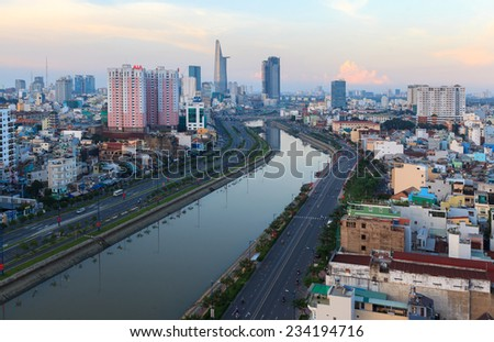 HO CHI MINH, VIETNAM - AUGUST 31, 2013 : Arial view at  Vo Van Kiet Highway in Ho Chi Minh city with the bridge cross the canal, buildings, houses and traffic at evening - stock photo