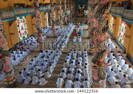 HO CHI MINH, VIETNAM - DEC 24: People praying in Cao Dai Temple on Dec 24, 2012, in Ho Chi Minh, Vietnam. Caodai is a Vietnamese religion mixing different religions from around the world.