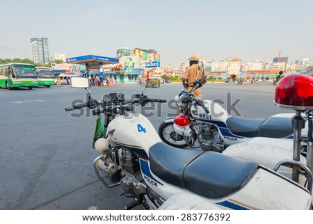 HO CHI MINH, VIETNAM - FEB 18, 2015: An unidentified traffic policeman inspects the road opposite the Ben Thanh Market on Tet. Tet is Lunar New Year in Vietnam. - stock photo
