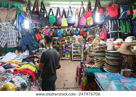 HO CHI MINH, VIETNAM - JAN 15, 2015: An unidentified man chooses wear at the Ben Thanh night market. It is popular among tourists as one can buy here various goods especially local souvenirs. - stock photo
