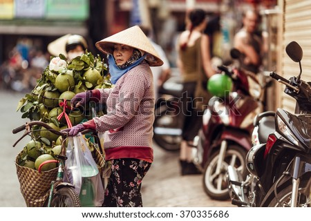 HO CHI MINH, VIETNAM - JAN 15, 2016: the Vietnamese woman sells cocoes on the street in Hochiminh (Saigon) on the sunset. Saigon is the largest city in Vietnam - stock photo