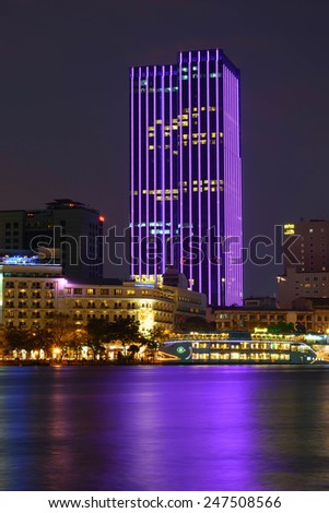 HO CHI MINH, VIETNAM - JANUARY 26, 2015 : Enjoy the Time Square building (buildings running lights seven colors) from the other side of the Ben Nghe canal in Ho Chi Minh City (Saigon), Vietnam. - stock photo