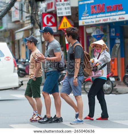 HO CHI MINH, VIETNAM - JULY 6, 2014: Unidentified Asian tourists cross the road followed by a street pedlar woman. Street pedlars in Pham Ngu Lao usually sell small souvenirs and trifles. - stock photo