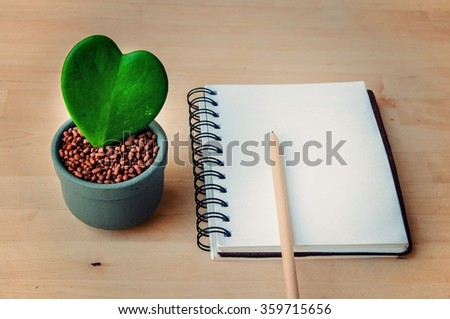 Ho ya plant with pot / Heart shaped plant / with a pen and sketch book on wooden background. Image shallow depth of field. - stock photo