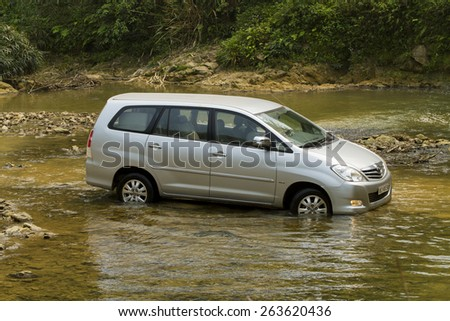 Hoa Binh, Viet Nam - March 19, 2015: Toyota Innova car crossing the river in Vietnam