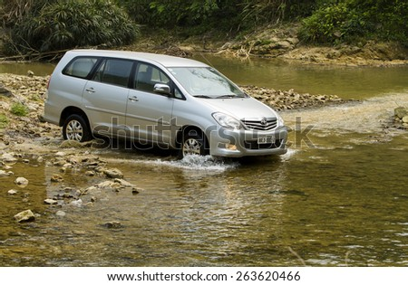 Hoa Binh, Viet Nam - March 19, 2015: Toyota Innova car crossing the river in Vietnam - stock photo