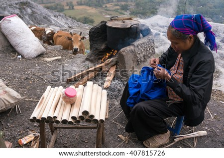 HOA BINH, Vietnam, January 12, 2016 Thai ethnic woman, sits embroidery, the pot of food, with a cow in the distance stood watching. peaceful scene