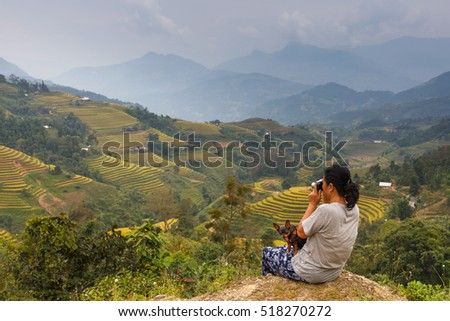 Hoang Su Phi, Ha Giang province, Vietnam - September 30, 2016 :  The woman and her chihuahua pet dog, they are viewing the terraced rice fields which has beautiful view of the northwest mountains, VN