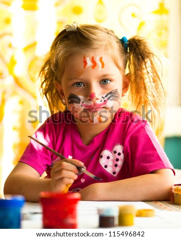 Hobby: Child, drawing paint with paint of face. - stock photo