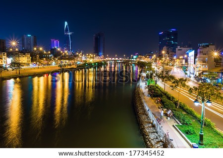 HOCHIMINH CITY, VIETNAM - FEBRUARY 15:Night city view from Ben Nghe canal in Hochiminh city on February 15, 2014. Hochiminh city is the biggest city in Vietnam - stock photo