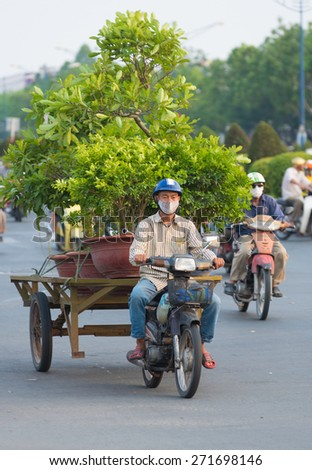 HOCHIMINH, VIETNAM - APRIL 19, 2015: An unidentified motorcyclist drives several garden trees in Truong Chinh Street during rush hours. The main means of cargo transportation in Vietnam is motorcycle. - stock photo