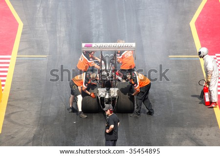 HOCKENHEIM - AUGUST 16 : An unidentified team gets ready for qualifying session at nitrolympics drag racing event August 16, 2009 in Hockenheim,  Germany. - stock photo