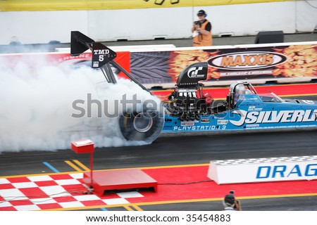 HOCKENHEIM - AUGUST 16 : Driver Dave Wilson performs a burnout during qualifying at nitrolympics drag racing event August 16, 2009 in Hockenheim, Germany. - stock photo