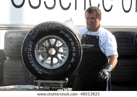 HOCKENHEIM, GERMANY - CIRCA 2010: A crew member washes down a Formula 1 wheel to prepare for the new season of Formula 1 racing on March 14, 2010. - stock photo