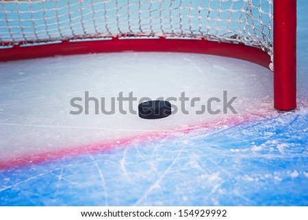 Hockey puck crossing red goal line. Close view - stock photo