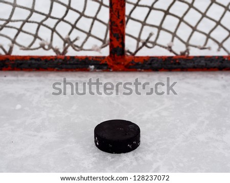 Hockey puck in net - stock photo