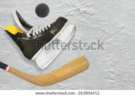 Hockey skates, stick and puck on the ice. Texture, background - stock photo