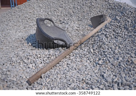 Hoe and clam-shell shaped basket on pile crushed stone at construction site - stock photo