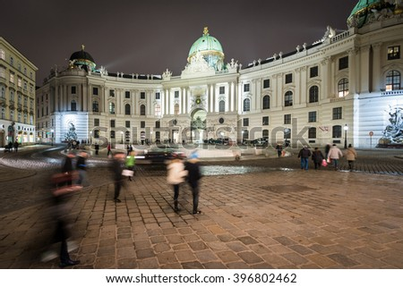 Hofburg Palace in centre of Vienna. Official residence and workplace of Austria President. Night scene with tourists walking near building. Europe travel. - stock photo