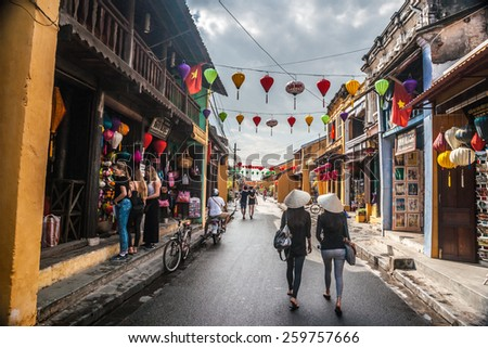 HOI AN, VIET NAM - FEBRUARY 4, 2015: Two unidentified asian female tourists in traditional vietnamese conical hats walk on a street in Hoi Ah on Feb 4, 2015. Hoi An is a World Heritage Site