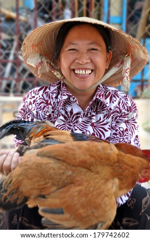 HOI AN, VIETNAM - APRIL 16, 2009: A happy vendor offers a live chicken for sale in the markets of Hoi An in central Vietnam. - stock photo