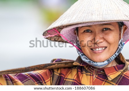 Hoi An, VIETNAM - DECEMBER 4: Vietnamese woman in Asian conical hat smiling. 52% of people work in agriculture. Rice as main crop exporting to 70 countries. December 4, 2012, Hoi An, Vietnam, Asia. - stock photo