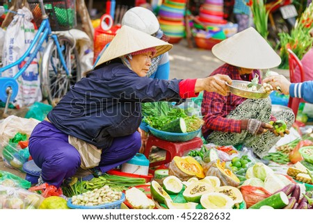 Hoi An, Vietnam - February 17, 2016: Asian woman in traditional vietnamese hats selling fresh vegetables in the street market in Hoi An, Vietnam.