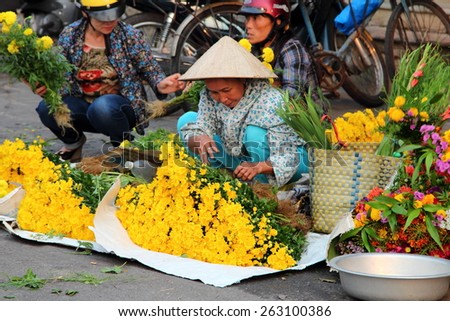 HOI AN, VIETNAM - MARCH 19, 2015: A Flower vendor selling fresh flowers at local market in Hoi An. - stock photo