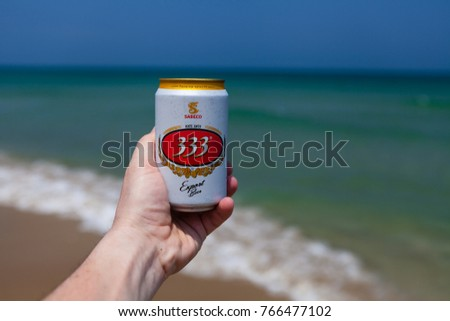 Hoi An, Vietnam - march 15 2017: hand holding can of cold 333 beer against emerald ocean and blue sky