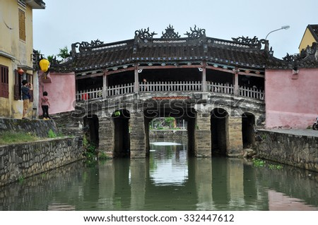 HOI AN, VIETNAM - MARCH 3, 2013: Tourists visiting the famous Japanese Bridge in the city of Hoi An, an important Southeast Asian trading port in the past - stock photo